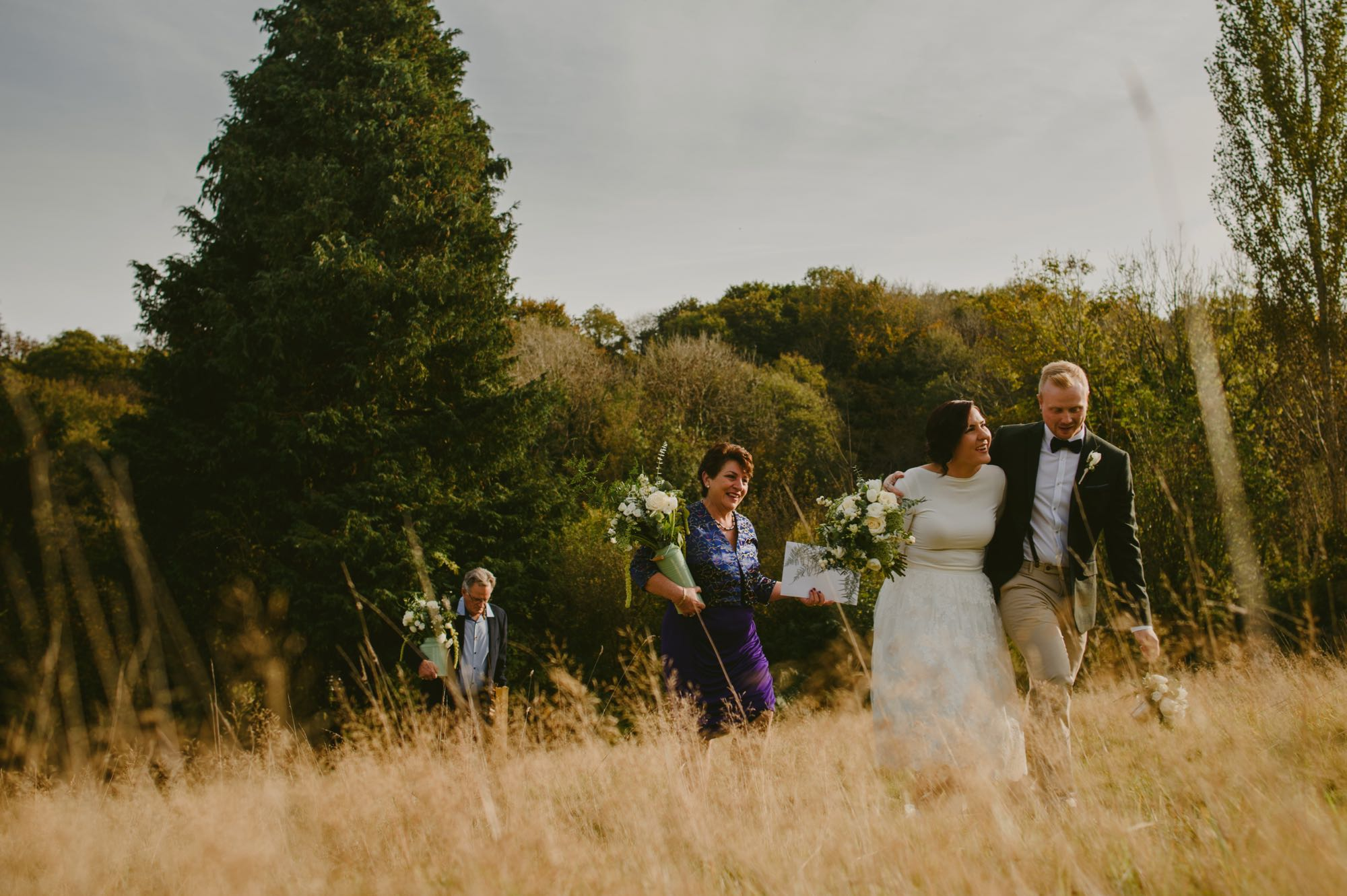 This photo is taken in the meadow with a wedding party of 4 people making their way up a slope from the Lake Arbour. The grass in the meadow is long, parched and golden. There are many trees in the backgorund and they are showing their autumn colours. The couple are in out front walking. The groom is on the left and the bride is on the right. The groom has his arm around his bride's shoulders. They are facing the camera. The bride's bouquet of white flowers and green foliage is in her right hand. The bride is wearing a knee-length, full-skirted, a-line dress. She has dark hair which she is wearing up. The groom is wearing chinos, brown brogues, a dark jacket a pale blue shirt and a dark bow-tie. He has light brown hair. Following behind the couple are the bride's parents. Her mum is wearing a purple pencil skirt with a v-necked silk blouse. Her dad is behind her mum ans is wearing a dark jacket and open necked blue shirt. Both are carrying a large vase of white flowers with green foliage.