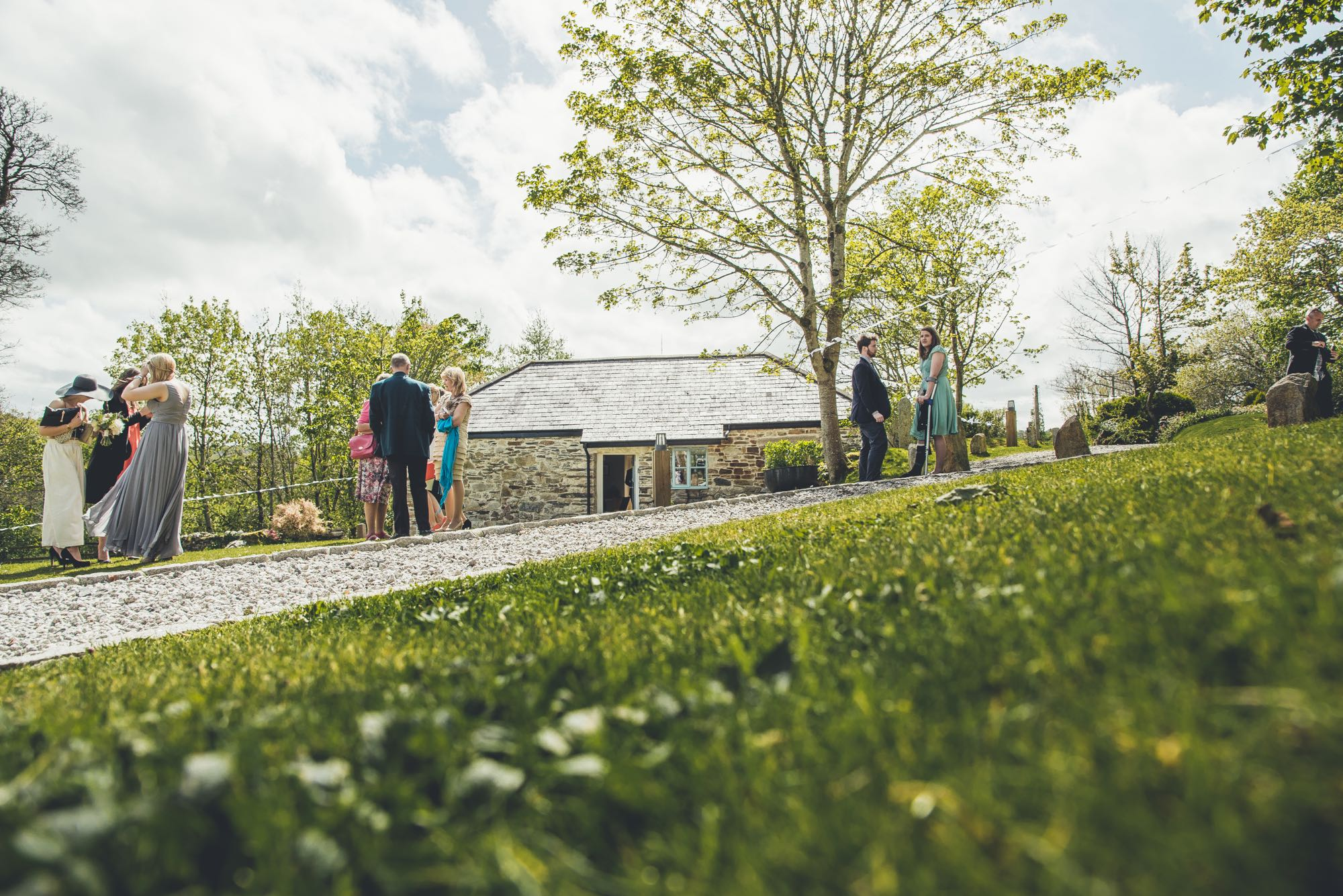 This is an image of some guests relaxing in the grounds. In the middle of the picture you can see cottage number two which is a sleeps two cottage. This cottage is detached and is made of local granite stone which is gray and brown. It has a gray slate roof. There is a door in the middle of the cottage and the door is open. There is a casement window to the right hand side of the door. In the foreground of the picture there is grass and diagonally across the picture there is a gravel pathway sloping upwards. The sky is blue but cloudy. It is a spring day and the trees are partially in leaf. There are trees to the left and to the right of the cottage. On the left of the picture at a distance of about 20 meters from the camera are 3 guests standing in a group. In the middle of the picture, also about 20 meters from the camera, is another group of 4 guests. Towards the right of the picture also at about 20 meters from the camera is another group of 3 guests.