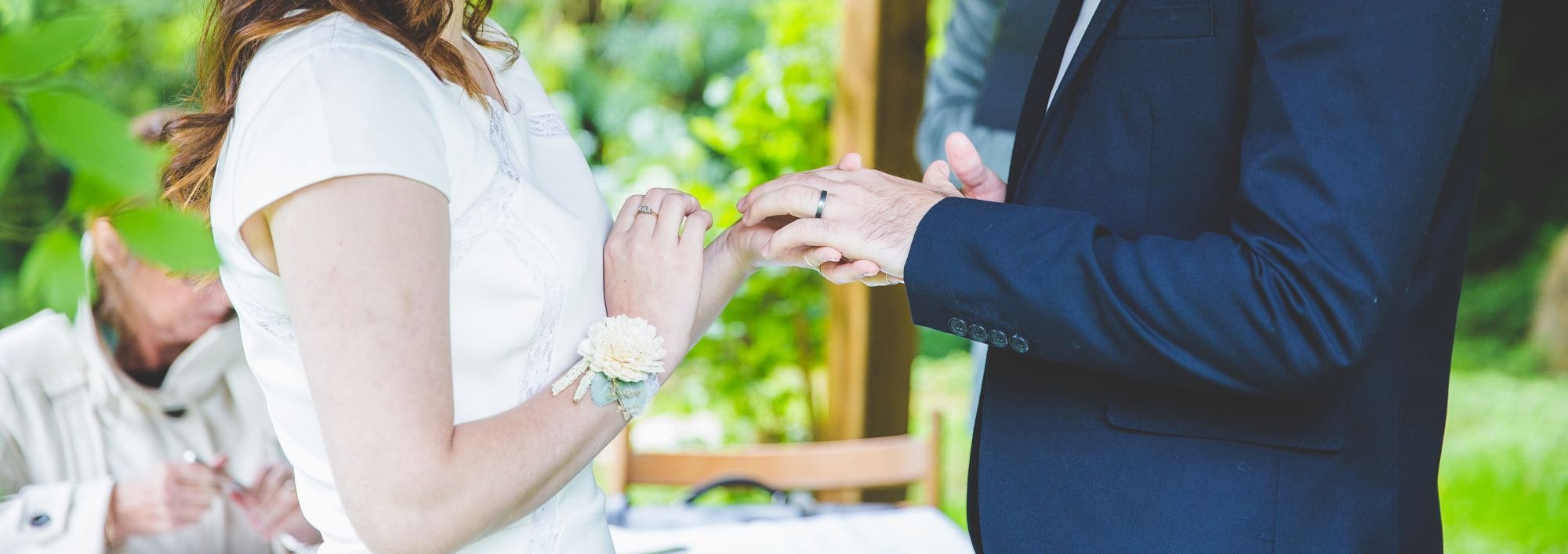This image shows an elopement couple exchanging rings. You can only see the middle section of the couple (from the waist to the neck) and it is a close-up, detail shot. The bride has just placed the ring on her groom's finger. The bride is wearing a cap-sleeved, white dress and has a flower on her wrist. She has long, dark hair that she's wearing loose. The grooom group is wearing a dark blue suit. In the background there are lots of green trees, shrubs and grass. On the left you can see part of the registrar's assistant. She is seated, placing the lid on a pen. The registrar is just visible behind the groom. He is standing and wearing a gray suit. You can see part of the wooden arbour structure and the registrar's table and a wooden chair.