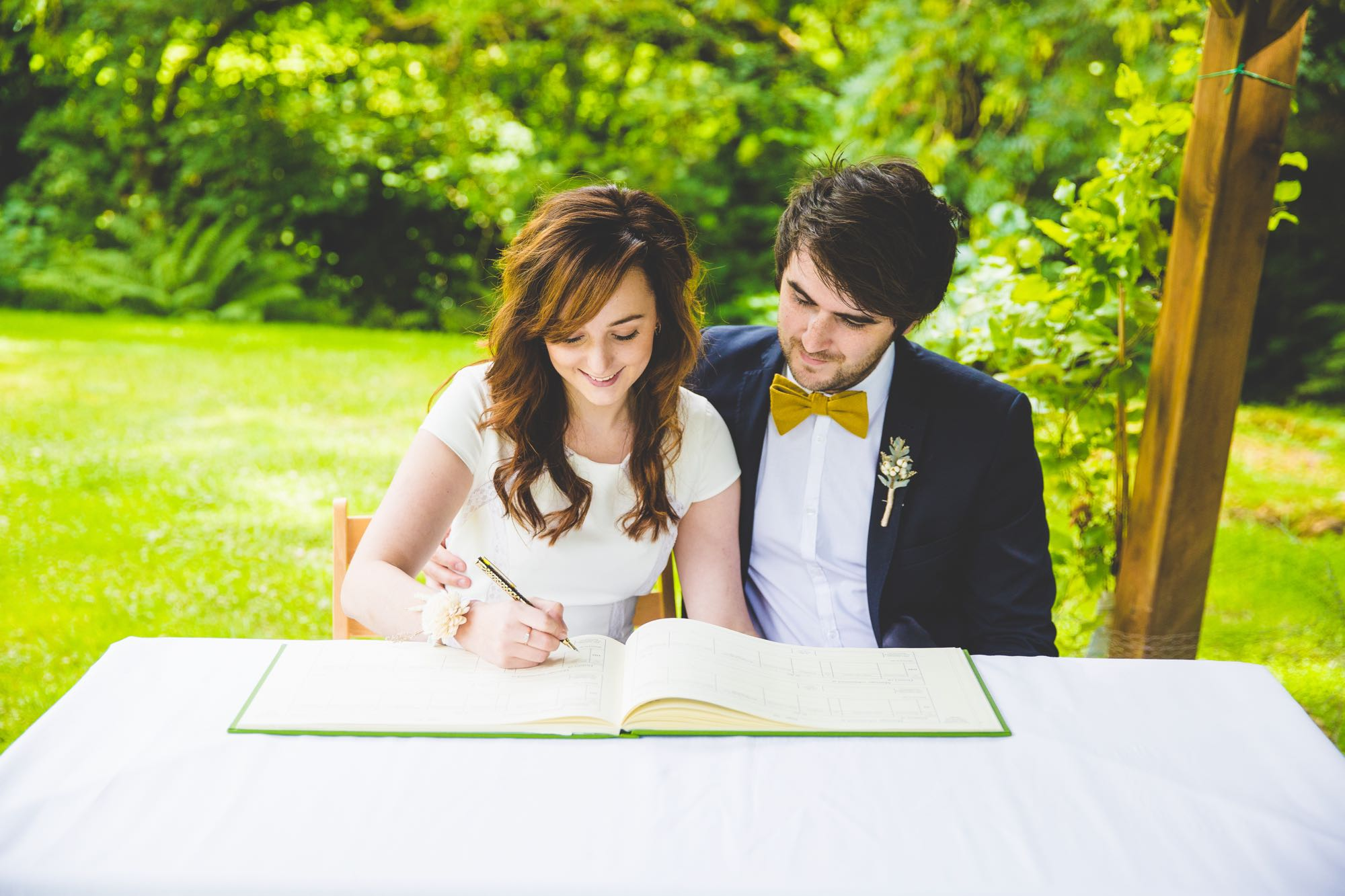 This image shows an elopement couple signing the register. The couple are seted at a white clothed table. In front of them is the open register. The bride sits on the left and the groom on the right. They are both looking at the book and the bride has a pen in her right hand. The groom has his arm around the bride's waist. The bride is wearing a cap-sleeved, white dress and has a flower on her wrist. She has long, dark hair that she's wearing loose. The groom is wearing a dark blue jacket, a white shirt and a yellow bowtie. He has dark hair and a beard. In the background there are lots of green trees, shrubs and grass. On the right you can see one of the oak posts that form part of the Lake Arbour.