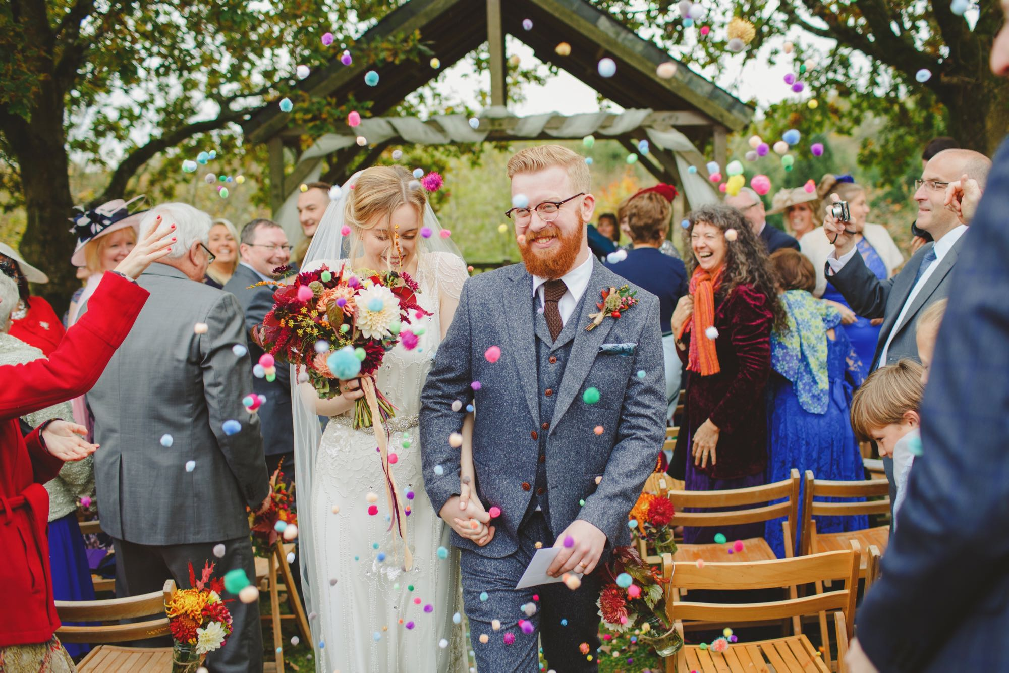 Newly weds leaving the Oak Arbour. The arbour is a wooden structure with four corner posts supporting a pitched roof. The front of the arbouris draped with cream voiles.This photo shows a couple just walking away from the Oak Arbour after their ceremony. Their guests are thowing pompom confetti. The couple are in the foreground and the shot shows them from the knees up. They are holding hands and the groom is on the right, the bride on the left. The bride is wearing a white fitted dress with lace details and lace cap sleeves. She has dark blond hair she is wearing. The bride is wearing a veil. In her left hand she is holding a bouquet of autumn coloured flowers: red, golds and browns flowers. The groom is wearing a grey, tweed, three-piece suit with a, white shirt and a brown tie. The groom has red hair, glasses and a beard. The couple are holding hands and the bride is looking down and smiling and the groom is looking off to his left and also smiling. You can see some guests around them. The guests are looking mostly at the couple but some have their backs to the couple. There are rows of chairs set out in front of the arbour but the guests are standing. You can see the registrar standing in the background under the arbour..