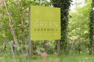 "This image shows the sign at the entrance to The Green. The sign is in the middle of the photograph. The sign is square and is lime green in colour. There is a pale dandelion clock motif in the background. There are the words in ""The Green House and Cottages"" written in white font. The word ""Cornwall"" is written in black font. This sign is mounted on two wooden posts. The ground around the sign is grass. And there are many trees and shrubs in the background."