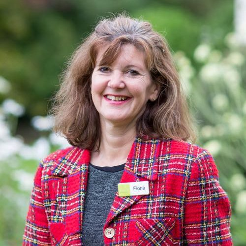 This is a picture of Fiona. Fiona is an event manager and sales manager. This is a head and shoulders shot of Fiona standing outside in front of some trees. She is wearing a red tartan jacket and a grey top. She is wearing a name badge. Fiona has shoulder-length mid-brown hair and she is smiling.