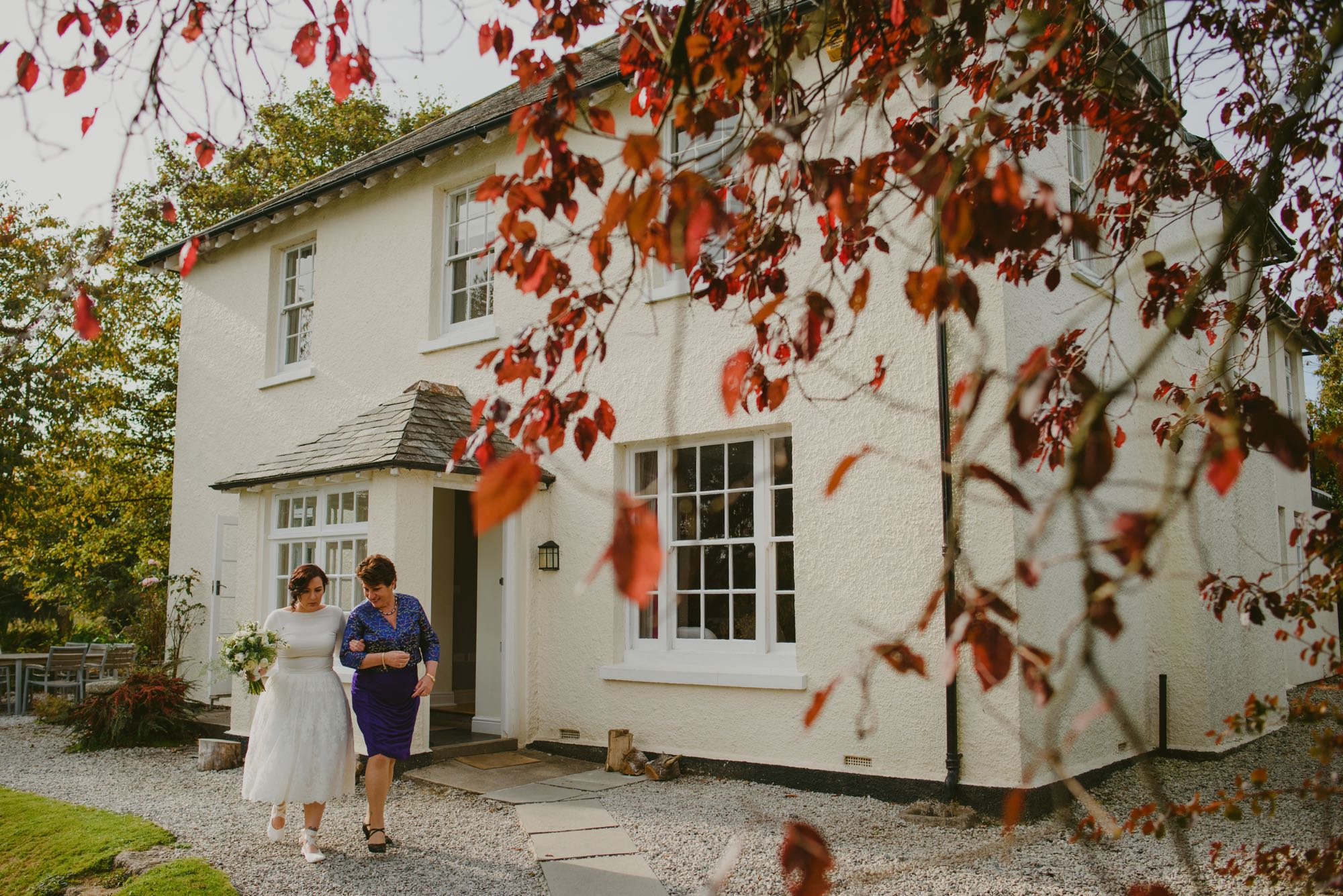 This is a picture of a bride and her mum beside the farmhouse walking towards the ceremony. The bride and her mum are in the left hand corner of the photo. The farmhouse takes up most of the image. The image is taken from just in front of the right hand corner of the house. There are some trees to the left with yellow autumnal leaves. There are some branches with russet leaves in the foreground. In the bottom left of the picture on the far side of the house you can seee some outside chairs and a table. The bride and her mum are walking away from the house, towards the camera along a gravel path. The farmhouse is rendered and painted white. It has a gray slate roof. The windows are georgian style sash windows and are painted white. There are three windows on the first floor and a French door on the ground floor which is open. There is a porch with two sets of georgian windows and a pitched slate roof. On the right hand side of the porch there is a open door. To the right of the porch there is another georgian style sah window. TThe bride is wearing a knee-length dress which has a full skirt but a fitted waist and bodice. It has a high neckline and long sleeves. The dress is white and she is wearing white, flat shoes. Her mum is wearing a purple pencil skirt and a purple, long-sleeved, v-necked silk blouse. The bride has long dark hair that she is wearing up. her mum has short dark hair.