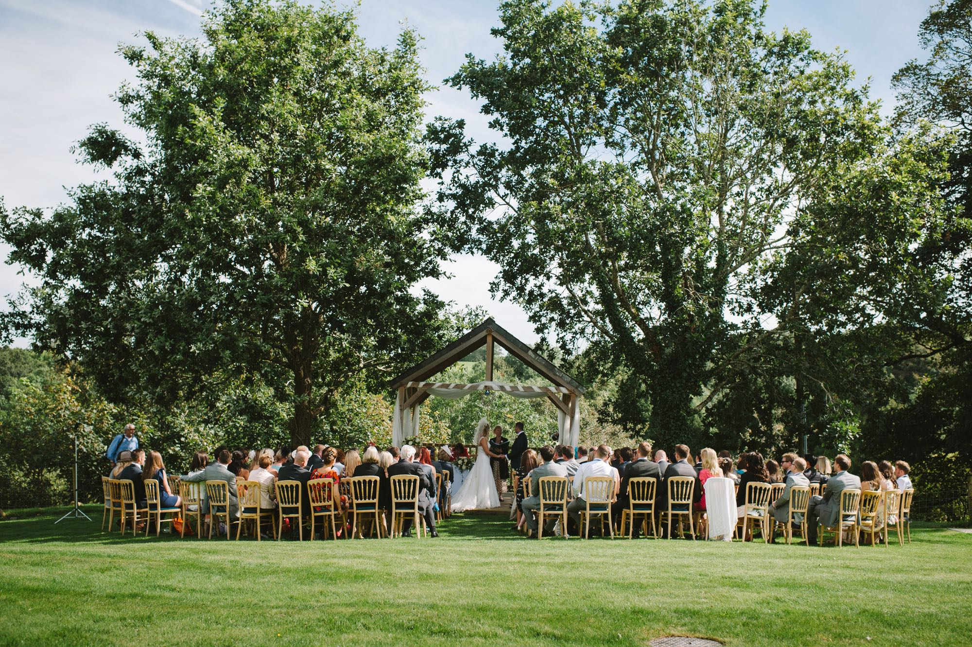 A couple exchanging vows under the Oak Arbour. The arbour is a wooden structure with four corner posts supporting a pitched roof. The arbour has a large Oak Tree on each side. The trees are in full leaf. This photo is taken from a bit of a distance and the whole of the Oak Trees are in the frame. The couple are under the arbour with the registrar and there is a clothed table (white) also under the arbour. The arbour is decorated with a some white voile. The couple are in the middle of the shot but are small compared to the canopy of the trees. They are holding hands and facing each other. The groom is on the right, the bride on the left. It is a summers day and the trees are in full leaf. The bride is wearing a white, full length, sleeveless, full-skirted dress. She has blond hair she is wearing down. The groom is wearing a dark suit. The couple are holding hands and looking at each other. You can see there guests sitting in front of the arbour in two columns of rows of seats.. The guests are looking at the couple towards the arbour and have their backs to the camera. You can see the registrar standing by a clothed table under the arbour with the couple.