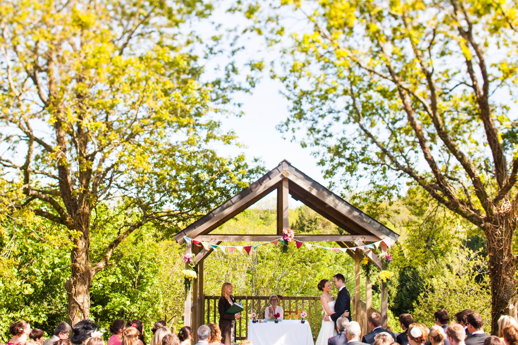 A couple exchanging vows under the Oak Arbour. The arbour is a wooden structure with four corner posts supporting a pitched roof. The arbour has a large Oak Tree on each side. The trees are in partial leaf. This photo is taken from a bit of a distance and most of the Oak Trees are in the frame. The couple are under the arbour with the registrar and there is a clothed table (white) also under the arbour. The arbour is decorated with bunting. The arbour is in the middle of the shot and the couple are standing in the right of the arbour. They are holding embracing and facing each other. The groom is on the right, the bride on the left. It is a spring day. The bride is wearing a white, full length, strapless, a-line dress. She has dark hair she is wearing up. The groom is wearing a dark suit. You can see top of their guests heads as they sit in front of the arbour in two columns of rows of seats.. The guests are looking at the couple towards the arbour and have their backs to the camera. You can seee the registrar holding a book in the right hand corner of the arbour and there is a white, clothed table under the arbour.
