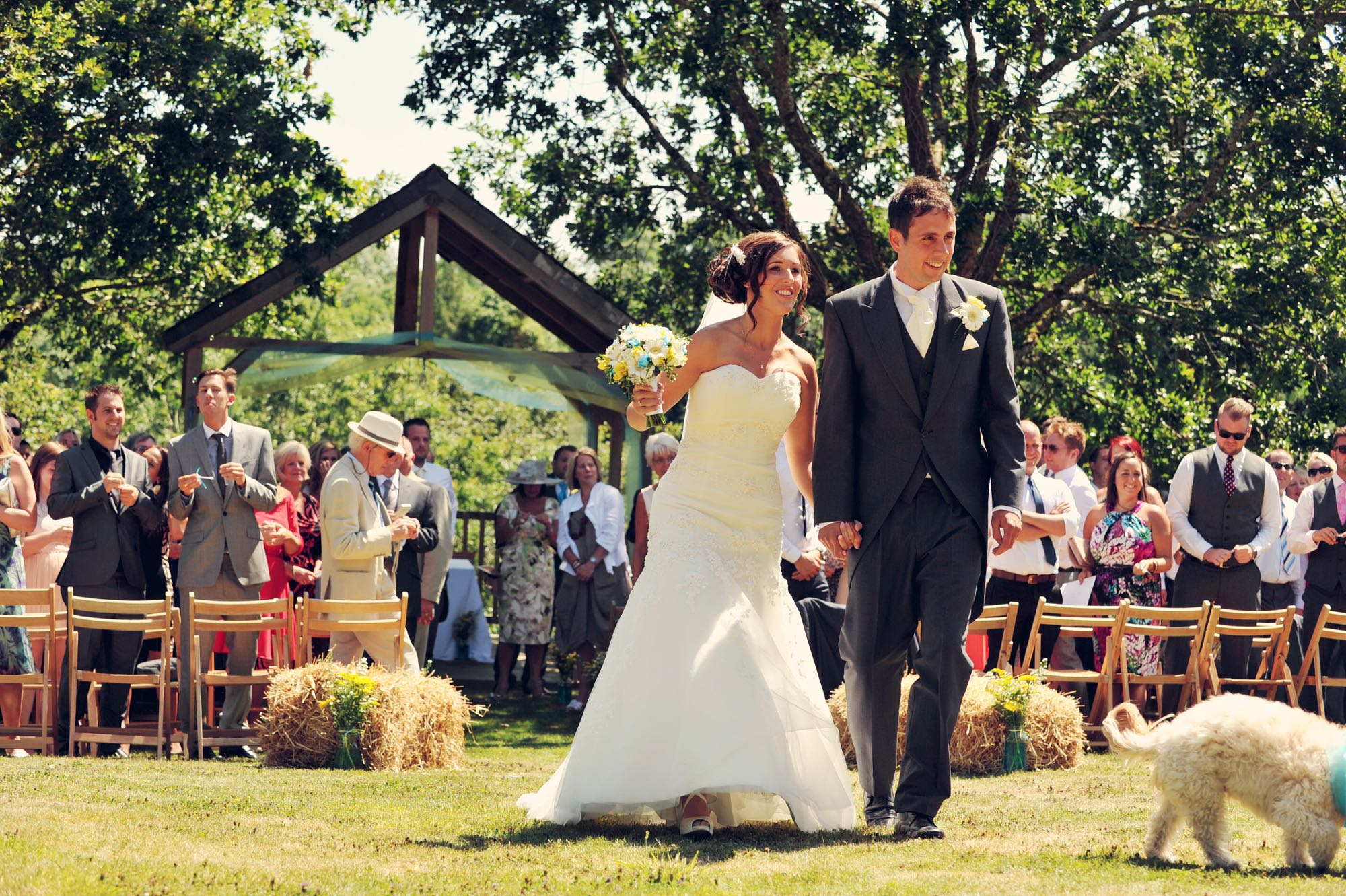 Newly weds leaving the Oak Arbour. The arbour is a wooden structure with four corner posts supporting a pitched roof. This photo shows a couple just walking away from the Oak Arbour after their ceremony. The arbour is decorated with a voile banner in tuquoise and yellow. The couple are in the middle of the shot, slightly offset to the right and the phot shows them in full length. They are holding hands and the groom is on the right, the bride on the left. Just slightly out of shot is the couples dog (you can't see his head). It is a summers day and the trees are in full leaf and the grass is parched. The bride is wearing an ivory, a-line, strapless dress. She has dark hair she is wearing up with a clip. In her right hand she is holding a bouquet of turquiose and yellow flowers. The groom is wearing a gray morning suit with white shirt tie. The couple are holding hands, smiling and looking forward and slightly to their left. You can see some guests in the background. The guests are looking at the couple and have their backs to the arbour. There are rows of chairs set out in front of the arbour with haybales at the end of the back rows. The guests are standing. You can seee the registrar standing by a clothed table under the arbour in the background.