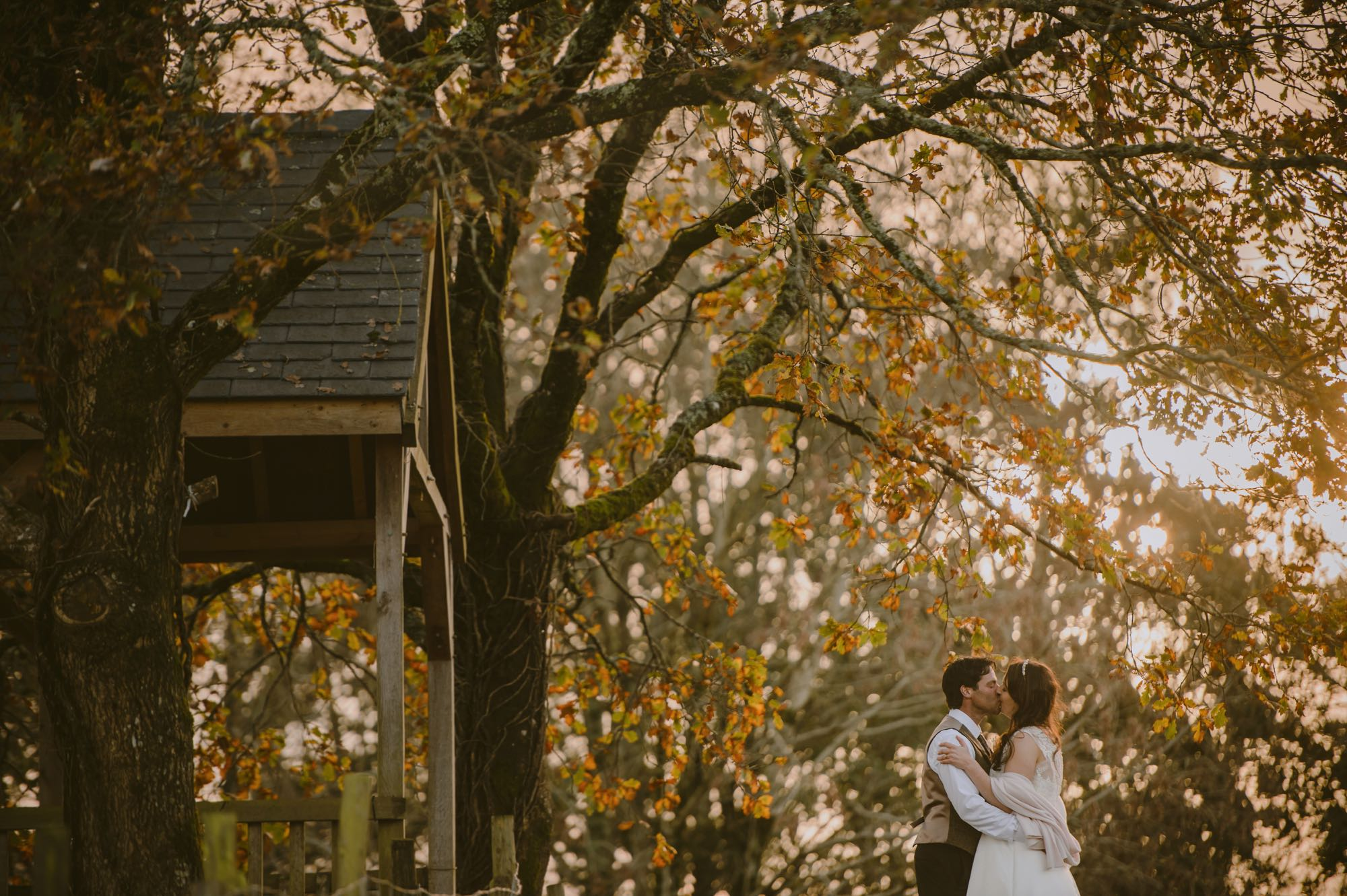 A couple having a romantic moment beside the Oak Arbour by themselves. This photo is taken side on to the arbour with the couple to the right of the shot. The arbour is a wooden structure with four corner posts supporting a pitched roof. The arbour has a large Oak Tree on each side. The trees are in autumn colours and the sun is shining through the branches. This picture is taken in the autumn. The couple are beside the arbour embracing. The couple are small compared to the trees and are shown from the knees up. The groom is on the left and the couple are embracing. The bride is wearing an ivory, short-sleeved, a-line dress. She has dark hair that she is wearing down. The groom is wearing a dark trousers a light bron waistcoat and has dark hair.