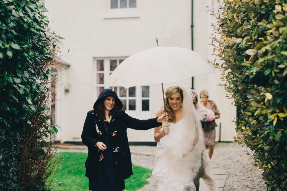 This image shows a member of the Green team staff holding an umbrella over a bride's head as she makes her way towards her ceremony. The picture is taken in front of the farmhouse. There is a bush on either side of the image framing shot. You can see the corner of the house in the background. The farmhouse is white and has Georgian style windows. The member of staff is on the left and she's wearing a blue duffle coat with the hood up as it is raining. She is holding a white umbrella above the bride's head. Both of them are smiling. The bride has dark blond hair that she is wearing loose. She is wearing a short sleeved white gown and a veil. The dress is long and layered and she is holding it up so she can walk. In the background, walking you can see two ladies who are part of the bridal party.