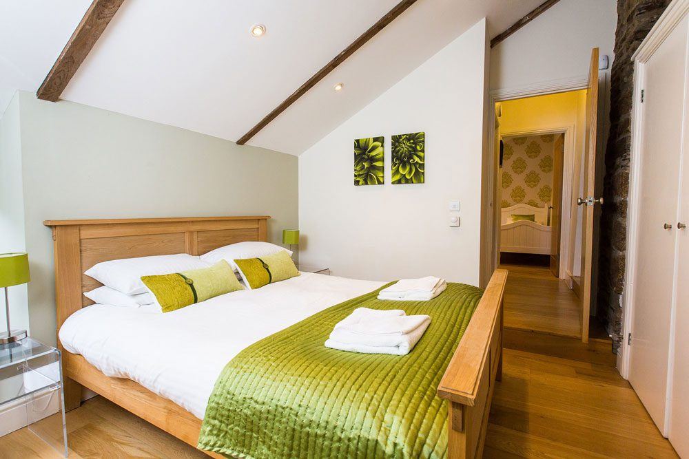 This is the double bedroom in cottage three which is a sleeps four cottage. The room has oak flooring. The wall behind the bed is painted pale green. There is a sloping ceiling with some old oak beams. There are spotlights in the ceiling and the ceiling is painted white. The door to the bedroom is open and through that open door you can see a single bed in another bedroom. The wall to the right of the photograph is exposed stone and there is a cupboard door in this wall. The cupboard door is painted white. There are two prints of dahlias which are lime green on the wall opposite to where the photograph has been taken from. Next to the bed there are glass bedside tables with bedside lamps with stainless steel posts and lime green shades. There is a king-size oak framed bed with white duvet cover and 4 pillows in white pillowcases. There are two lime green scatter cushions and a lime green throw along the end of the bed. There are some white towels folded on the bed. There is one step out up when exiting this room.