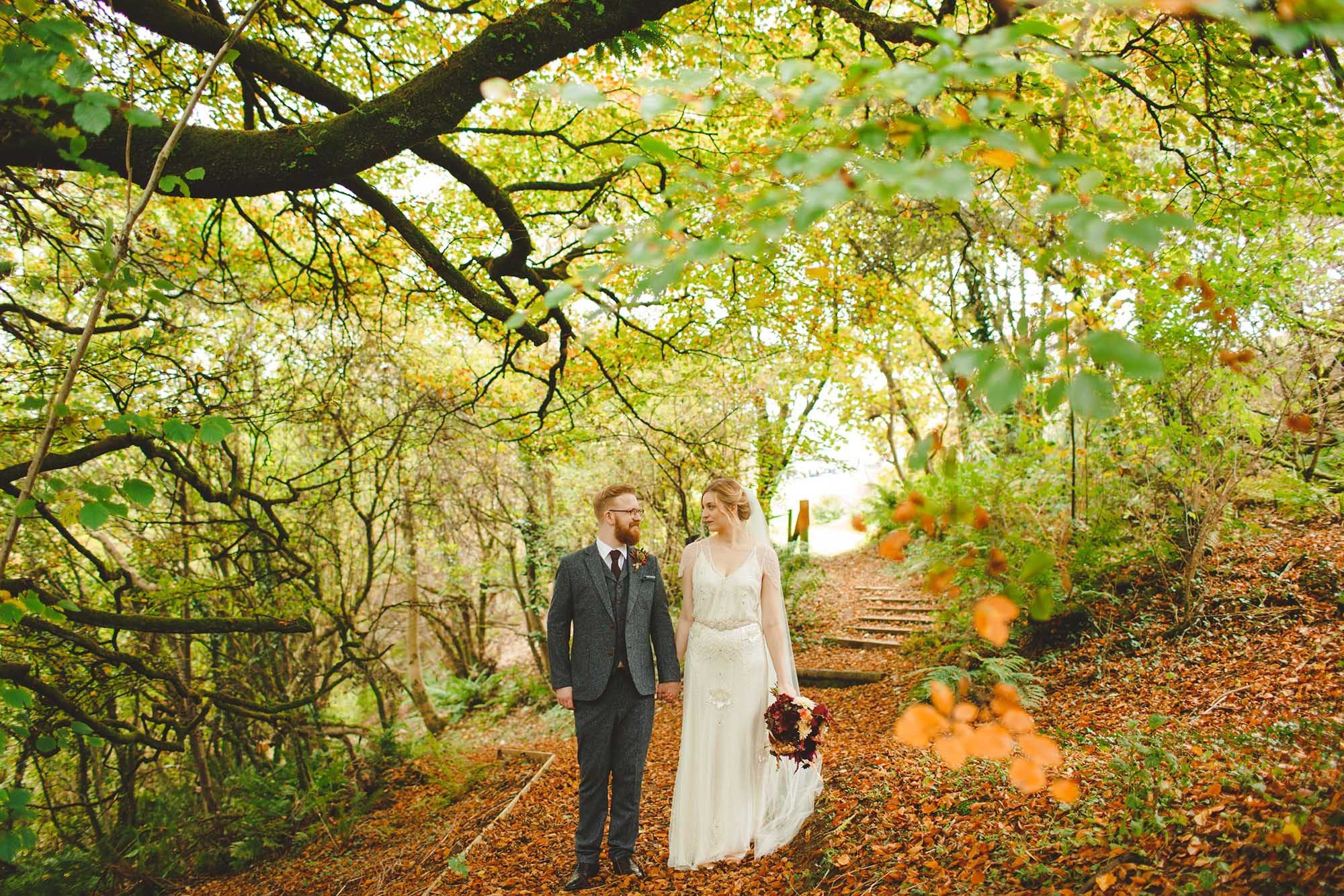 This is a photo of a bride and groom standing in a path in the woods in autum. This is a full length shot but the trees are about twice the height of the couple and form a canopy above their heads. There are loads of colourful autumn leaves on the ground but there are still green leaves on the trees. The bride is wearing a cream, full length, flowing dress with lace detail and lace sleeves she is wearing a veil. She has dark blonde here which she is wearing in a loose updo. The groom is wearing a grey, tweed three-piece suit with a white shirt and a brown tie. The groom has glasses and a full beard and he has red hair. In her left hand the bride is holding a bouquet with autumn coloured flowers; purple red and yellow. The bride is on the right of the shot and the groom is on the left. They are facing the camera but their heads are turned towards each other. There are some steps leading upwards out of the woods in the background to the right of the bride.