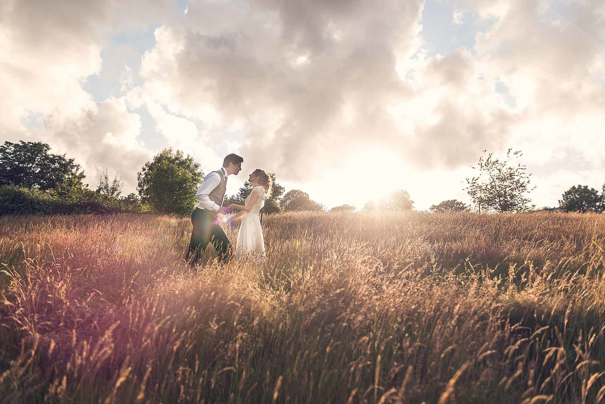 This is a summer wedding. The image is of the bride and groom in a field of long grass. The grass is parched fromthe summer sun. The couple are in the mid distance and it is a full length shot. They are slightly located off centre to the left of the photograph. Half of the images is of the grass and the top the top half is of the sky which is cloudy. There is a line of trees in the middle of the photo running accross the horizon. The bride and groom are facing each other and holding hands. The groom is leaning towards the bride. The groom wears dark trousers and a brown waistcoat. He wears a white shirt and a dark tie he has dark hair. The bride is wearing a white, full length dress. She has dark blond hair which she wears up loosely and is looking towards the groom.