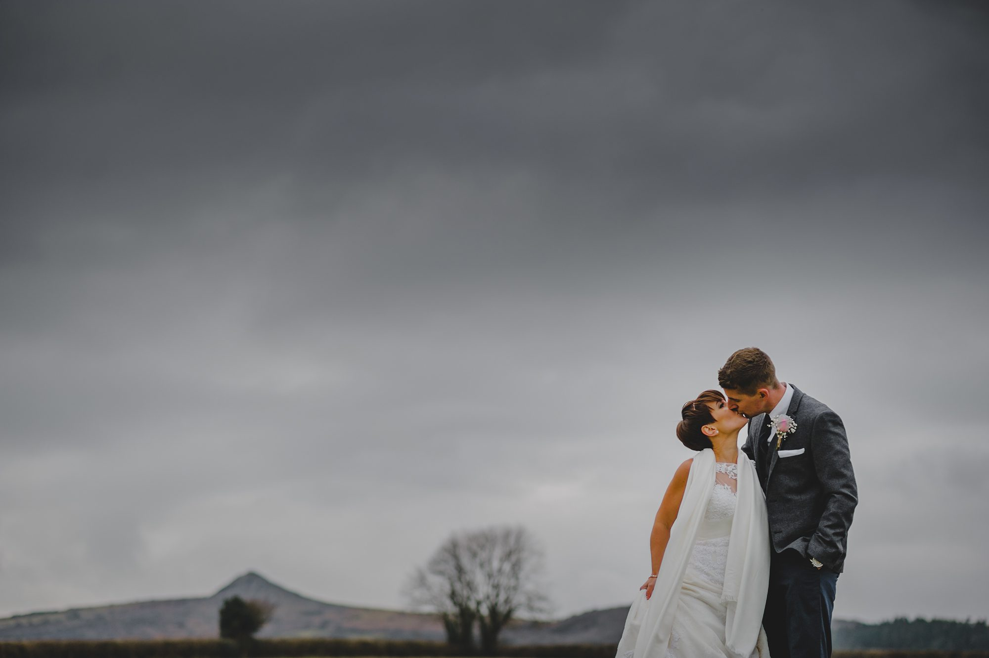 This image is a landscape shot with a couple in the bottom right hand corner of the shot. The image is predominantly of the sky. The sky is very dark and moody. On the horizon you can see the tors of Bodmin Moor. There are some leafless trees in the background on the horizon. The couple are close to the camera in the right-hand corner. The bride has short dark hair and is wearing a white, short sleeved gown with lace at the neckline. She has a stole around her shoulders. The groom is wearing a grey suit, a white shirt and a dark tie. The bride is turned towards the camera but her head is turned towards the groom. The groom is turning slightly towards the bride as they lean towards each other for a kiss.