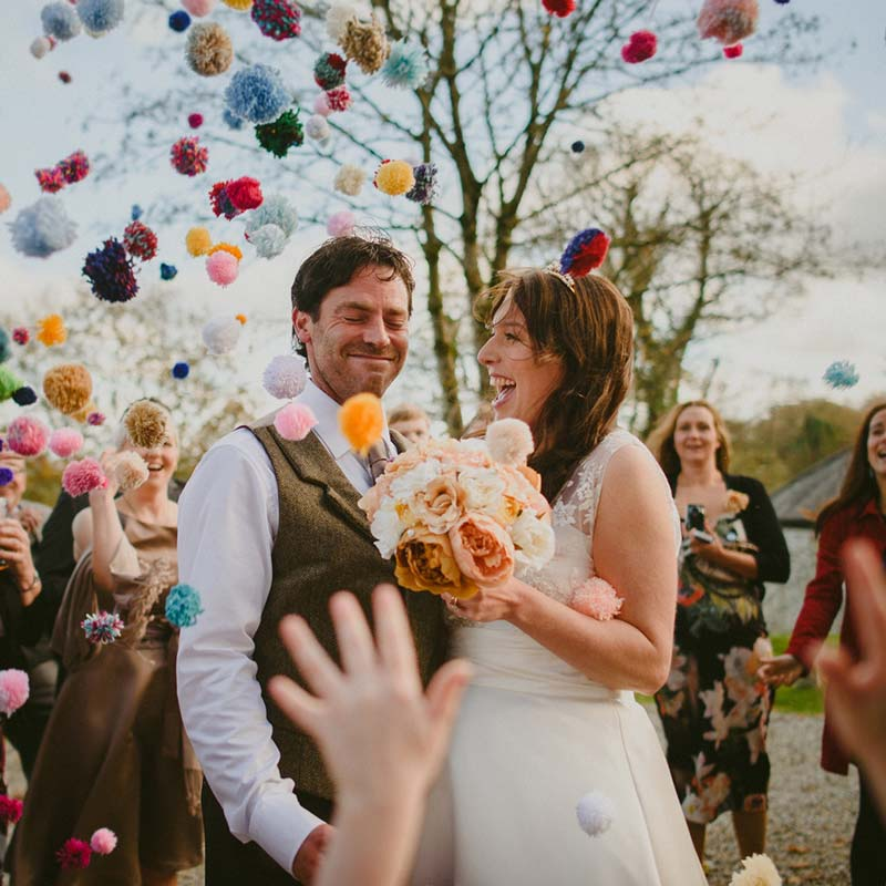 This image shows a bride and groom outside with some other guests standing around them. The guests are throuwing pompom confetti. The couple are in the foreground and the shot is from the knees up. The couple are standing side-by-side with the groom on the left and the bride for the right.The bride has dark hair which she is wearing loose. She's wearing an a-line sleeveless dress with the lace detailing at the shoulders. In her left hand she carries a bouquet of muted pink and white peonies. The groom has dark hair and is wearing a white shirt and a brown tweed waistcoat. The groom has his eyes closed and is smiling the bride is looking at her groom and laughing. In the background there are some trees without leaves. In the foreground there is a hand throwing confetti.