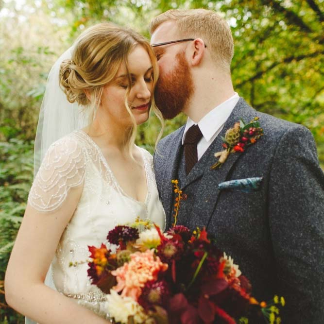 This is a close up photo of a bride and groom embracing in the woods. The bride is wearing a cream dress with lace detail and lace sleeves she is wearing a veil. She has dark blonde here which she is wearing in a loose updo. The groom is wearing a grey, tweed three-piece suit with a white shirt and a brown tie. The groom has glasses and a full beard and he has red hair. In her right hand the bride is holding a bouquet with autumn coloured flowers; purple red and yellow. The bride is on the left of the shot and the groom is on the right. The bride is turned slightly towards the groom and has her eyes closed. The groom is on the right and is leaning in towards the bride and is kissing her on the far side of her head. The bride has her eyes closed.