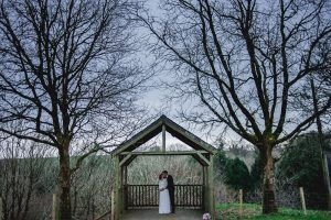 A couple having a romantic moment under the Oak Arbour by themselves. The arbour is a wooden structure with four corner posts supporting a pitched roof. The arbour has a large Oak Tree on each side. The trees are in bare and the sky is dark. This pictureis taken in the wintertime. This photo is taken from a bit of a distance with most of the Oak Trees in the frame. The couple are under the arbour embracing. The couple are centred in the shot at the bottom of the frame. The couple are small compared to the trees. The groom is standing behind the bride with his arms around her. The bride is wearing a white, full length, long-sleeved, a-line dress. She has dark hair that she is wearing up. The groom is wearing a dark suit and has dark hair.