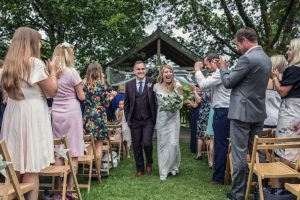 Newly weds leaving the Oak Arbour. The arbour is a wooden structure with four corner posts supporting a pitched roof. This photo shows a couple just walking away from the Oak Arbour after their ceremony. The arbour is decorated with a voile banner with stars on it. The couple are in the middle of the shot and the phot shows them in full length. They are holding hands and the groom is on the left, the bride on the right. The bride is wearing an ivory fitted dress with sparkles and lace details. It has cap sleeves. She has dark blond hair she is wearing loose. In her left hand she is holding a bouquet of green and cream flowers. The groom is wearing a dark brown 3-peice suit with gray shirt and a blue tie. The couple are holding hands, smiling and looking at each other. You can see some guests around them. The guests are looking at the couple and clapping and have their backs to the camera. There are rows of chairs set out in front of the arbour but the guests are standing.