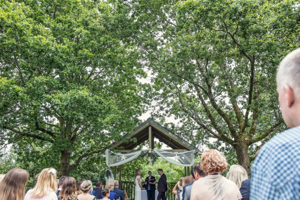 A couple exchanging vows under the Oak Arbour. The arbour is a wooden structure with four corner posts supporting a pitched roof. The arbour has a large Oak Tree on either side. The trees are in full leaf. This photo is taken from a bit of a distance with most of the Oak Trees in the frame. The couple are under the arbour with the registrar standing between them and there is a clothed table (white) also under the arbour. The arbour is decorated with a voile banner in cream with stars on it. The couple are in the middle of the shot towards the bottom of the frame and are small compared to the canopy of the trees. They are facing each other with the registrar between them. The groom is on the right, the bride on the left. It is a summer's day. The bride is wearing a white, full length, dress in ivory with capped sleeves. She has dark blond hair she is wearing down. The groom is wearing a brown suit. You can see their guests sitting in front of the arbour. You can only see the back of the guests heads as they are looking towards the arbour and have their backs to the camera.