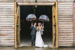 This image show s a couple standing in the doorway to the really rustic barn. The doors of the bar are open. The doors of the barn are very large the height is around twice the height of the couple. The doors open outwards. The couple stand just on the threshold and the barn looks dark on the inside. You can see two strands of festoon lighting inside the barn. The outside is clad in horizontal oak planks. The couple are holding their umbrellas above their heads. They are standing side-by-side, shoulder to shoulder facing the camera but looking at each other. The groom is on the left and the bride is on the right. The groom has dark hair and is wearing a gray three-piece suit with white shirt and white tie. The bride has blond hair which she is wearing up she has veil. The bride is wearing a fitted sleeveless full length white gown in silk. In her right hand she is carrying a bouquet with white flowers and greenery.