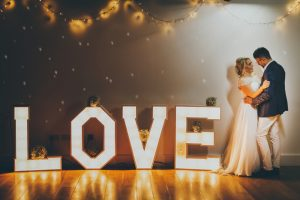 The main feature of this image is a large sign in light up letters spelling out the word LOVE. To the right of the sign a couple are standing embracing. This sign is set out on the floor and is almost as high as the couples' waists. The lights from the sign are reflected in the polished wooden floor. The wall behind the sign is in shadow and has sparkles and fairy lights on it. There are some bouquets placed randomly on the sign. These bouquets are made of gyp. The couple are embracing with the bride on the left and the groom on the right. She is wearing an a-line full length white gown with lace sleeves. She has blond hair that she is wearing in a loose up-do. The groom is wearing a grey jacket and chinos. He has dark hair. The couple are looking at each other and are side on to the camera. They are smiling.