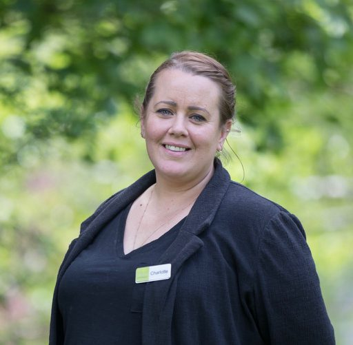 This is an image of Charlie who is one of our events staff. This photo is a close-up shot of Charlie from the waist up. In the background there are green trees. Charlie is wearing a black top and a black blouse over this. She is also wearing a name badge. She has dark hair and is wearing it up and she is smiling.