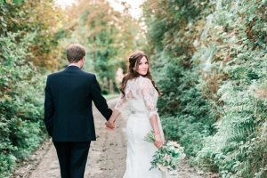 The bride and the groom are walking away from he camera down a narrow and leafy Cornish lane. The bride is on the right. She wears a fitted white gown with lace details and a delicate floral crown. The pic is takes from the back and the bride is looking over her right shoulder back at the camera. The groom wears a dark suit. The bride holds a bouquet of white and pink flowers in her right and it is hand-tied.