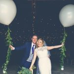 "This is an image of the bride and groom standing in the doorway of the Really Rustic barn. They are standing side by side with the groom on the left. The bride is leaning slightly inwards towards the groom. The bride has a bouquet of greenery in her right hand. The couple each have their outside arms outstretched and each is holding a very large white balloon tethered by a ""string"" of greenery. The groom is wearing a navy suit, gray waistcoat, white shirt and blue tie. The bride wears a full-length, sleeveless, white dress with lace details and a beaded bodice."