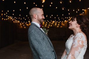 The couple standing in the doorway of the Really Rustic barn. The picture is taken from the waist up. Yoc an see festoon lighting in the background The are facing each other side on to the camera and holdinghands. The bride dark hair worn up. She has a fitted white dress with a sweatheart neckline and lace sleeves. The groom is wearing a tweed 3 piece suit and brown bow-tie.
