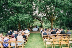An outdoor ceremony under the Oak Arbour with guests state don the lawn