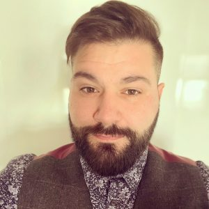 A head an shoulders shot of David our events manager. David is wearing floral shirt and waistcoat. He has brown hair swept over in a side parting and a beard.