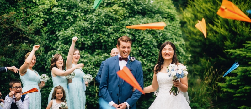 The image shows the bride and groom standing surrounded by trees with some guests around them. Their guests are throwing paper aeroplanes instead of confetti. The aeroplanes are in bright colours. There trees behind the couple who are standing. The trees are in full leaf. The image shows the couple from knees up. The bride is wearing a beaded, full-skirted, strapless dress. In her left hand she is holding a hand tied bouquet with blue and white flowers. She has dark, long hair that she's wearing down. The couple are facing the camera and smiling. The groom is wearing a light blue three piece suit with a brown bow tie and a white shirt. In the background you can see a little girl and little boy and three bridesmaids. The bridesmaids are wearing mint green, knee-length bridesmaids dresses. Their hands are raised as they throw the aeroplanes.
