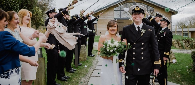 A couple walk away from the green room bar under the arch formed by swords. While they walk away their guests throw pom-pom confetti at them them. The bride is on the left and the groom is on the right. The groom where is a naval dress uniform. The bride wears a white, floor length gown with shoestring strap white and carries white and green flowers. The Green Room is a wooden chalet style building with glass frontage. This is an April wedding and the sky is overcast.