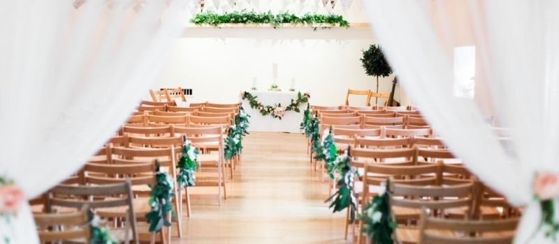 A shot of the wedding barn with oak floors and a-frame beams. There is greenery decorating the shelf at the back and also the edges of the 2 rows of folding wooden chairs. In the foreground there are 2 draped voiles with floral (pink rose) tie back.